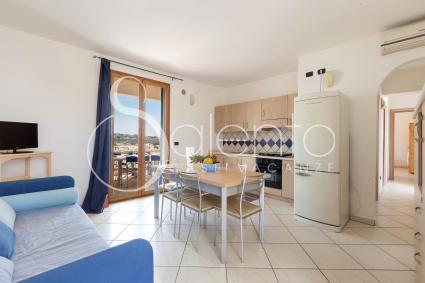 Il living con divano a due posti, cucina a vista e sala da pranzo