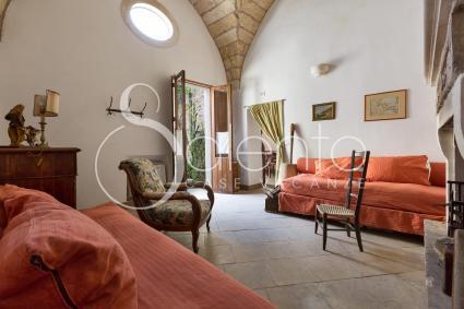 Il soggiorno con due divani letto e un bellissimo caminetto in pietra, luogo di pace