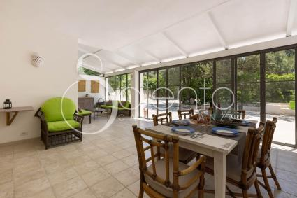 covered porch with lounge and dining room, with glass walls