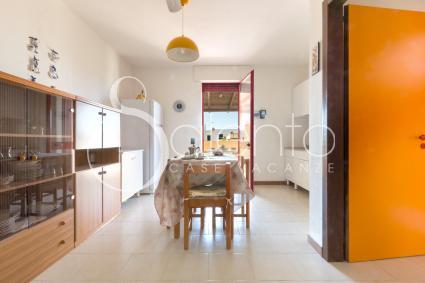 La sala da pranzo con tavolo e cucina a vista, nella casa vacanze sul mare di Torre Pali