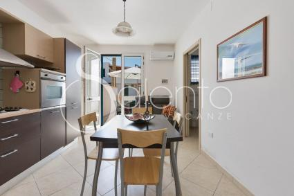 The living room is air-conditioned and has a well-equipped open kitchen