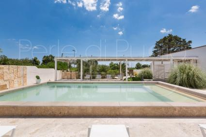 The beautiful pool is framed by a furnished solarium area