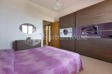 The double bedroom is characterized by the violet and mauve shades