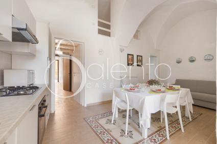 La zona giorno è arredata con cucina a vista, sala da pranzo e divano relax