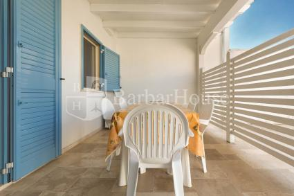 L`ampia veranda è arredata con tavolo e sedie per momenti di relax all`aperto