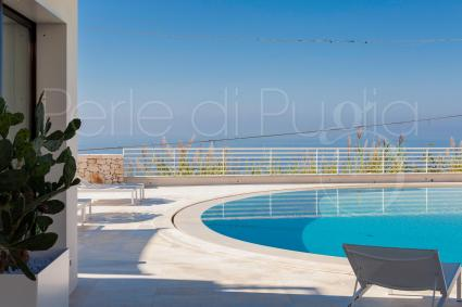 relaxing by the pool while enjoying the extraordinary sea view