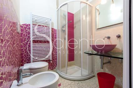 Il bel bagno fucsia e bianco con mosaici