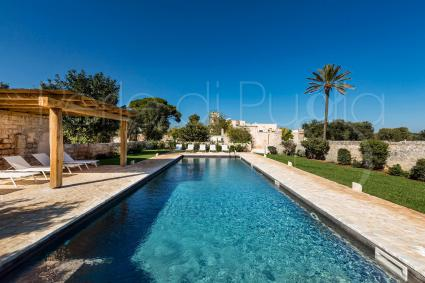 The beautiful swimming pool is framed by the area with beach beds