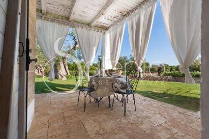 La verandina ombreggiata con tende in lino chiaro e tavolo in ferro battuto
