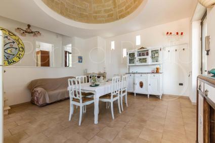 Una cupola in pietra accoglie nel soggiorno, arredato con sala pranzo e divano più tv